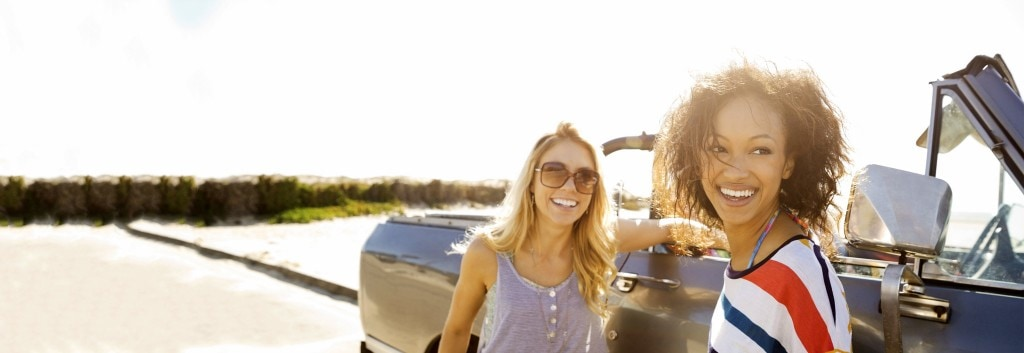 Two women smiling, one with smooth, dry hair and the other one with curly, dry hair, next to a car.