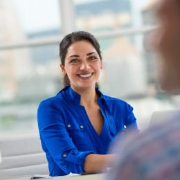 A smiling woman in a bright blue shirt sitting next to a desktop computer monitor.