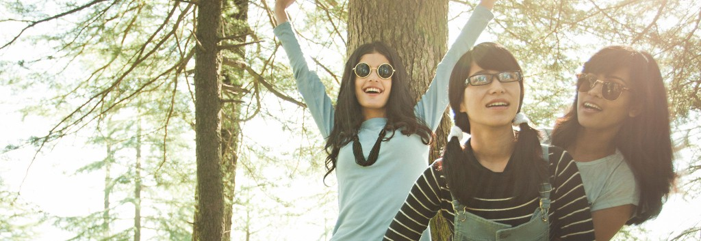 Three young, cheerful women with long, thick, black hair standing around in a sunny woodland.