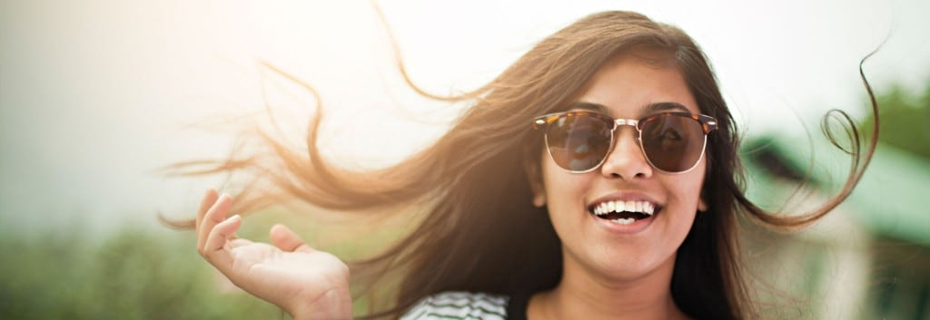 A smiling woman wearing sunglasses, her wavy, black hair flowing gently in the wind.