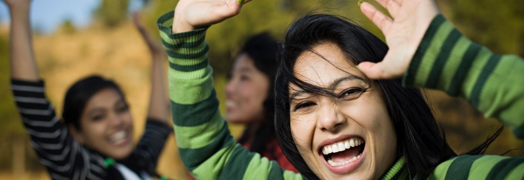 Three women joyfully throwing their hands up in the air while they laugh and smile.