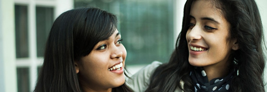 Close-up of two women with thick, black hair looking at each other while having a conversation.