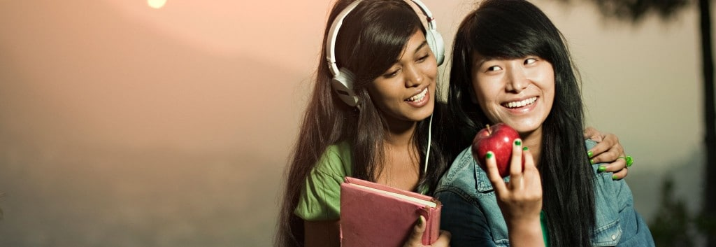 Two women with thick black hair. One is holding a red apple, the other is wearing large headphones and looking over the first's shoulder.