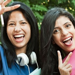 Four women laughing and making two-fingered peace gesture at the camera. One of the girls is wearing large headphones and holding a school notebook.