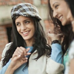 Close-up of a smiling woman in a stylish chequered hat.