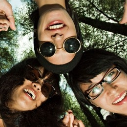 Three friends holding hands in a circle, leaning in over the camera. Behind and above them there is a canopy of tree tops.