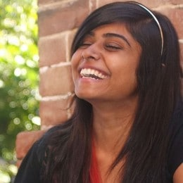Two women sitting outside, laughing  and gently high-fiving each other.