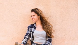 Happy woman with smooth long hair leaning against a wall.