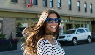 Model with thick, brown hair, wearing blue sunglasses is smiling as she crosses the street.