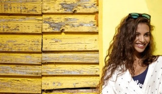 Young woman with long wavy brown hair, leaning against a yellow wall and smiling.